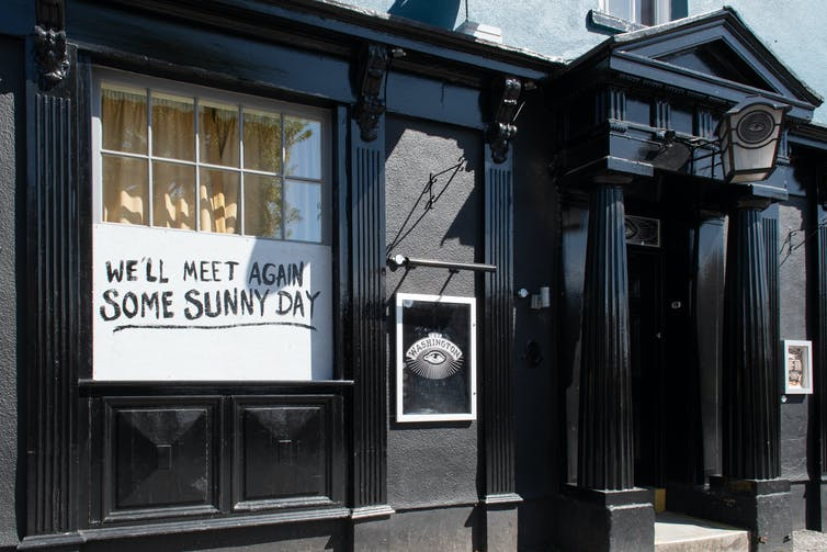 A closed UK pub with message 'We'll meet again some sunny day' in window during lockdown