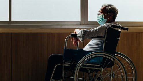 A man in a wheelchair and a mask on his own looking out of the window