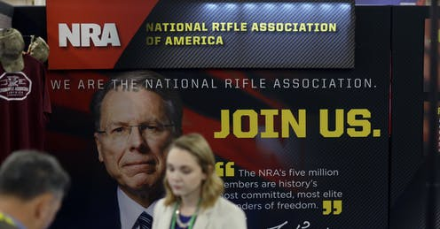 Woman stands next to an NRA poster.