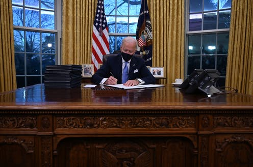 President Joe Biden signs a document in the Oval Office