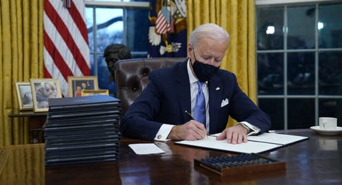 Biden, wearing a mask, signs executive orders in the Oval Office.