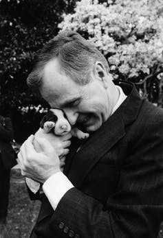 George H.W. Bush cuddles a very young puppy.