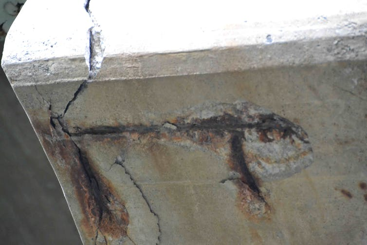 Degraded concrete and exposed rebar on a bridge
