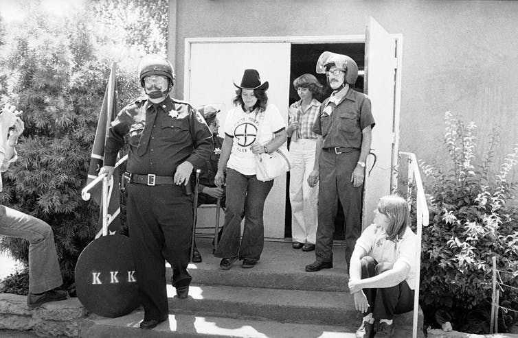 Ku Klux Klan security guards escorting two women members.