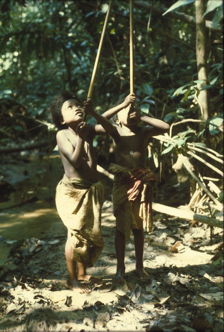 Two girls playing with blowpipes