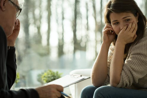 A woman, appearing depressed, with a therapist.