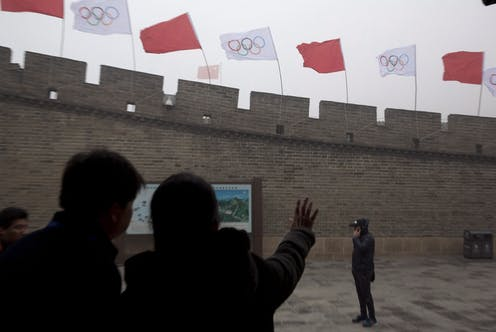 People look up at flags on a section of the Great Wall of China