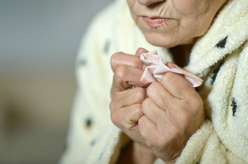 Cold, older woman clutching a handkerchief.