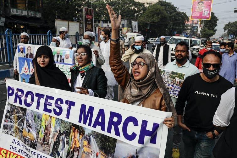 Three women carry a poster during a protest march.