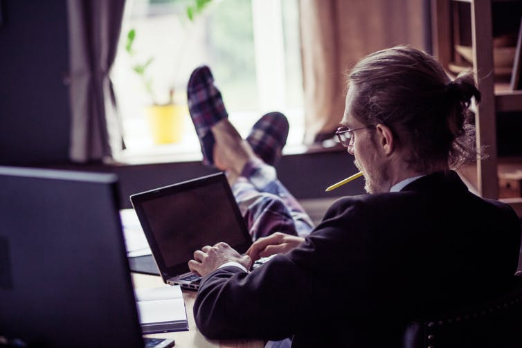 Man at home with laptop, suit and slippers on. Feet on desk.