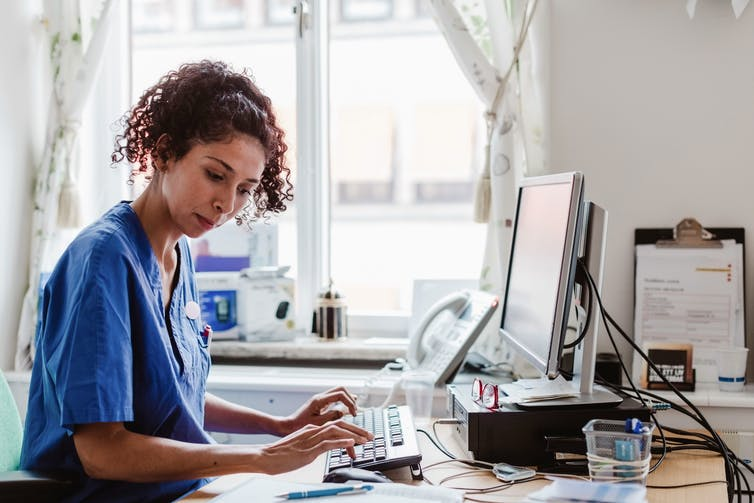 A nurse making a computerized medical report.