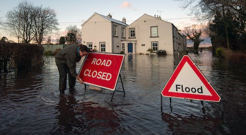 Woman putting 'road closed' sign up in flooded street.