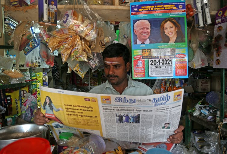 Indian man in shop reads newspaper with headlines and calendar about Joe Biden inauguration