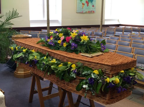 A wicker coffin decorated with beautiful flowers sitting in an empty church.