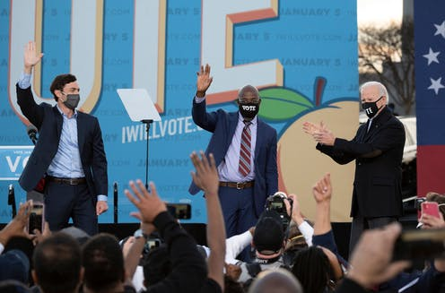 Ossoff and Warnock wave at a crowd of supporters, while Biden claps