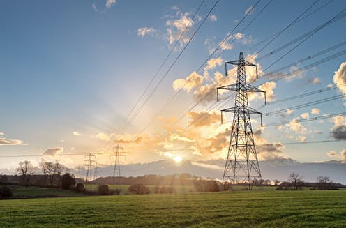 Electricity pylon in field with sunshine
