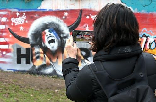 A woman photographs a mural depicting the 'QAnon Shaman.'