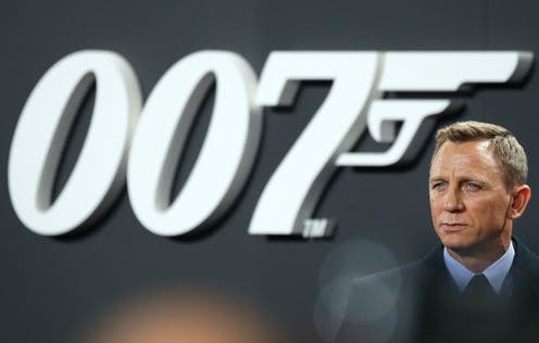 Daniel Craig wearing a suit and standing to the left of large 007 backdrop in black and white