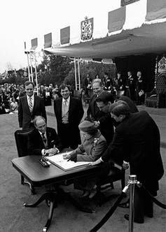 Queen Elizabeth sits at a small table and  signs Canada's constitutional proclamation with Prime Minister Pierre Trudeau sitting at her side.