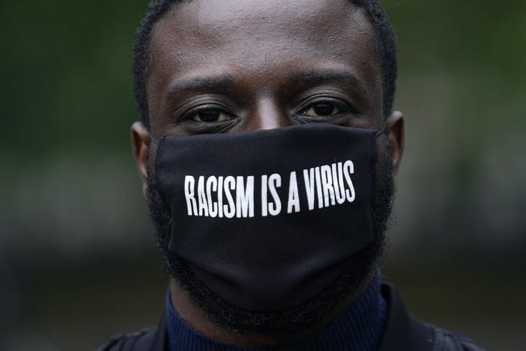 A man wears a black mask that says 'Racism is a virus'