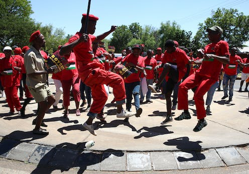 A group of men and women, dressed in red, form a circle, some leaping into the air, one crooked leg higher than the other, as they dance.