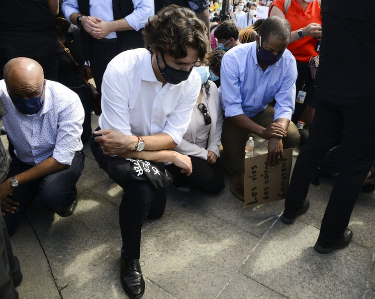 Justin Trudeau, in a mask, kneels on one knee.