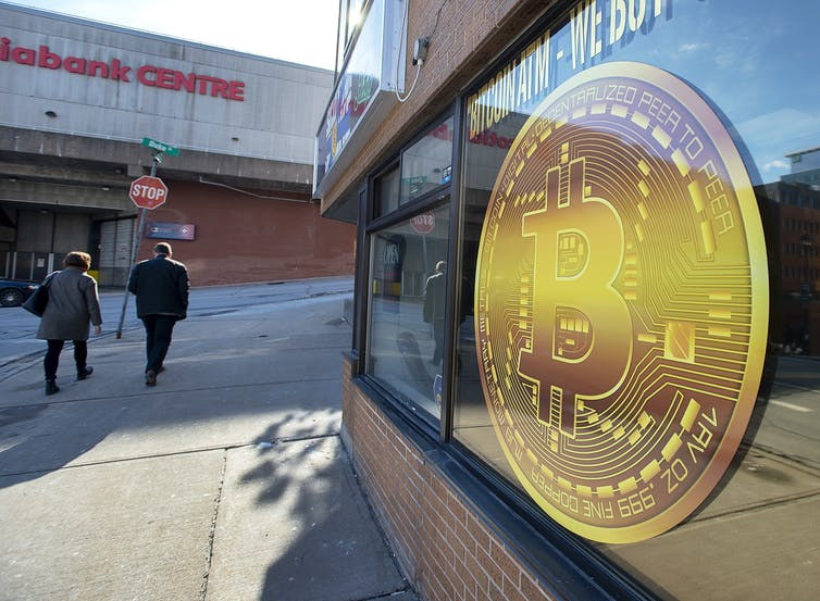 A sign advertises a Bitcoin ATM.