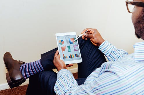 A man looks at financial graphics on his tablet.
