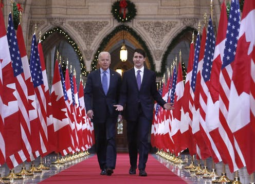 Biden and Trudeau walk down a red carpet flanked with Canadian and U.S. flags.