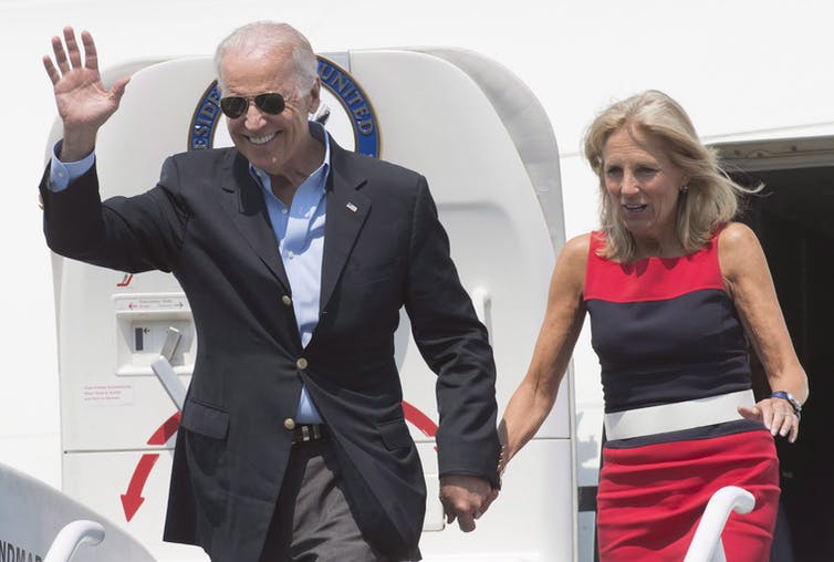 Joe and Jill Biden wave as they exit a plane.