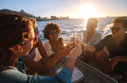 Affluent young people clink glasses on a boat at sunset
