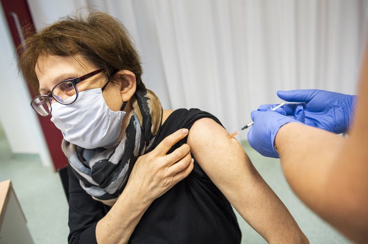 A health-care worker receives the Pfizer vaccine in Hungary.