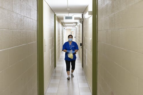 A woman in scrubs and a face mask in a long, narrow hallway