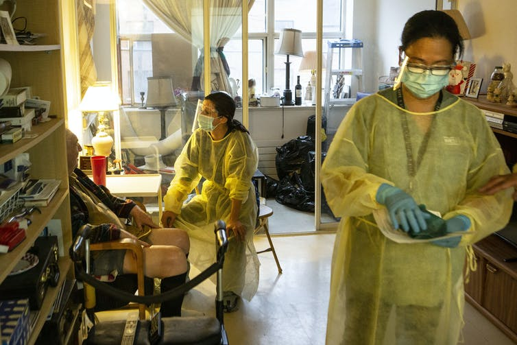 Two women in PPE and an elderly man sitting in a chair