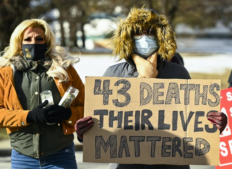 A woman and a man in face masks and winter coats, holding a cardboard sign reading '43 dead their lives mattered'