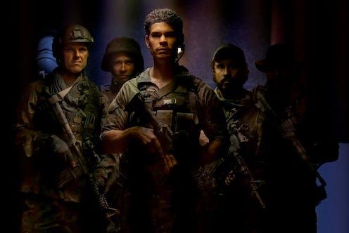 Screenshot: five soldiers look towards the camera
