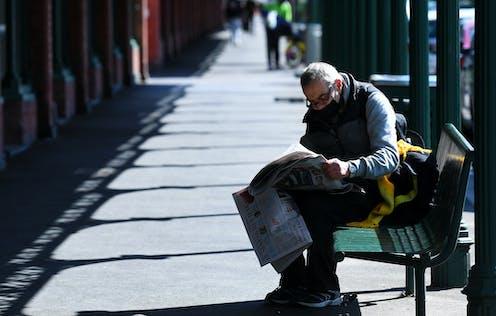 Man on bench reading newspaper