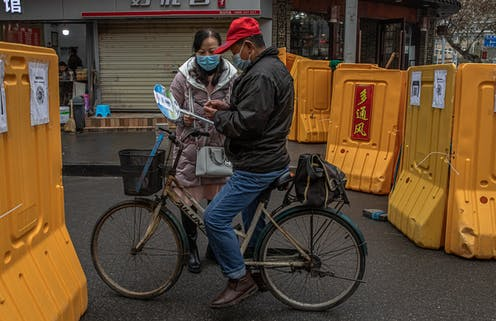 A checkpoint between two Wuhan neighbourhoods, where a health volunteer collections information from those passing through