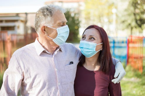 A couple in masks and gloves walking outside