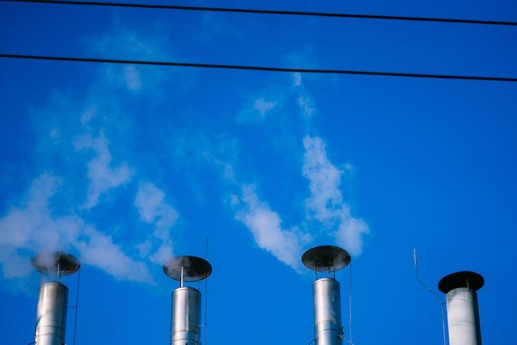 Four smokestacks against a blue sky.