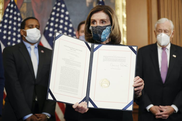 Nancy Pelosi wearing a COVID mask and holding up a folder containing the Article of Impeachment against Donald Trump, January 13 2021.