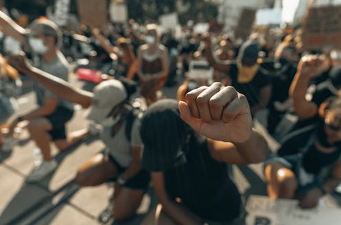 This image shows a close up a fist. All people in the photo are kneeling with raised fists.
