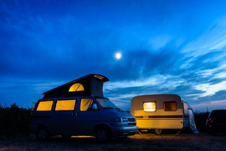 A caravan and camper van lit up at dusk.
