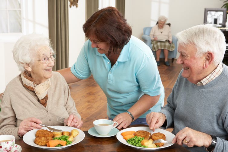 A woman chats with an elderly couple siting at a table having a meal