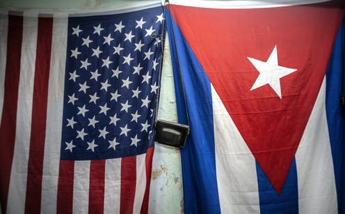 American and Cuban flags hang next to each other.