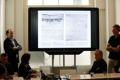 Handwritten pages are shown on a screen during a meeting.