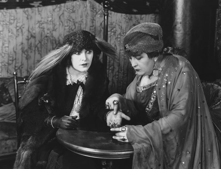 Two eccentrically-dressed women in a black and white photo, one reading the palm of the other