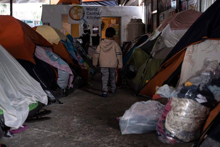 A migrant boy walks amid tents