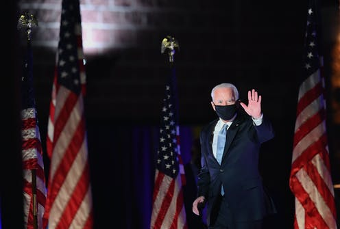 Biden walks in front of American flags while waving, in a black face mask