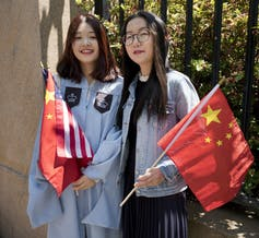 two women with U.S. and China flags, one wearing a graduation gown